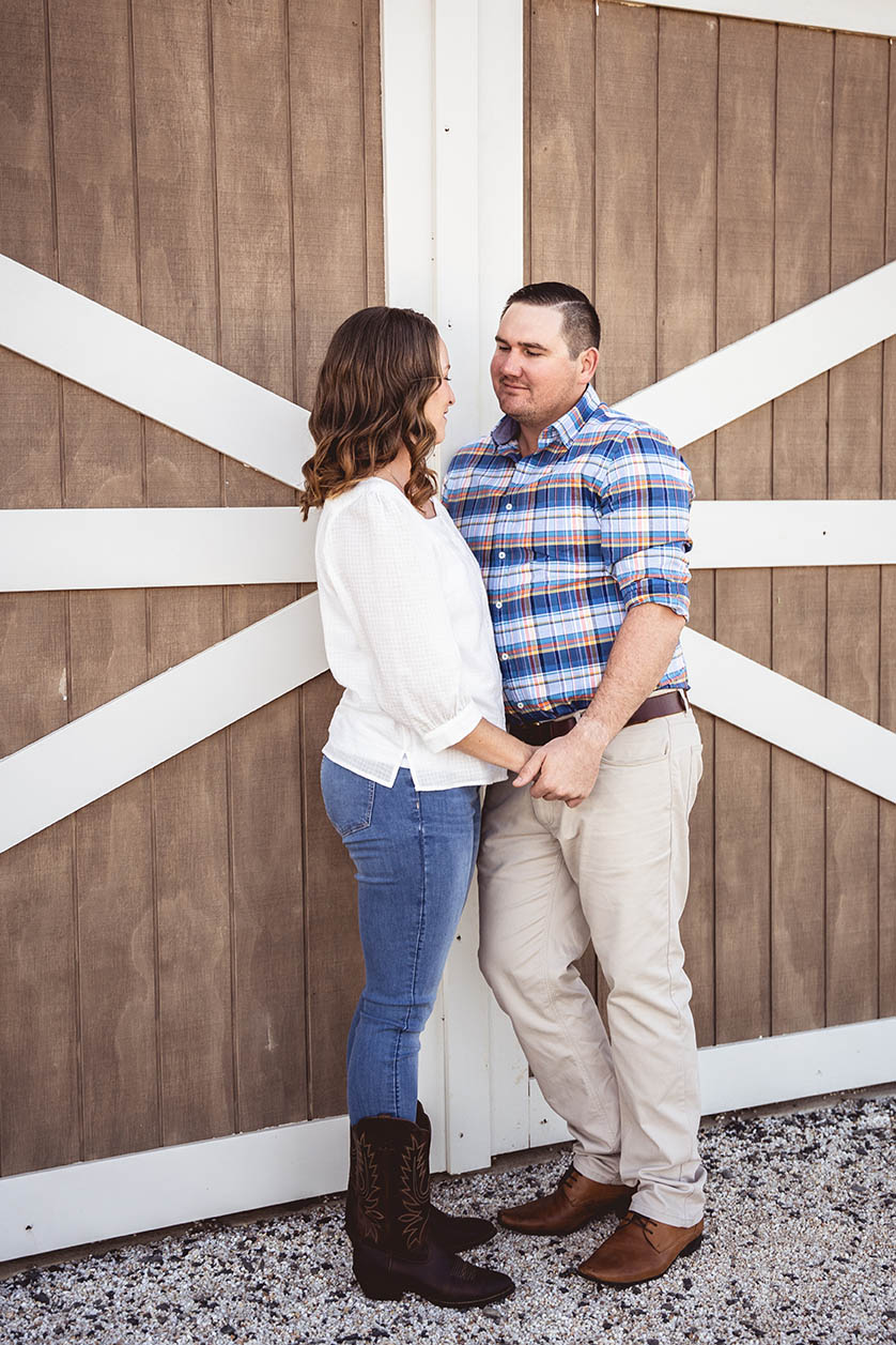 Engagement Photography - couple holding hands in front of barn
