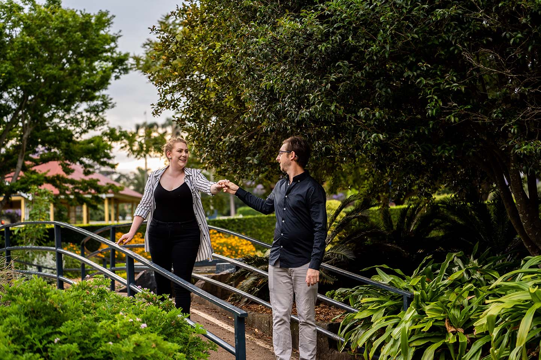 Engagement Photography - couple walking across bridge in park