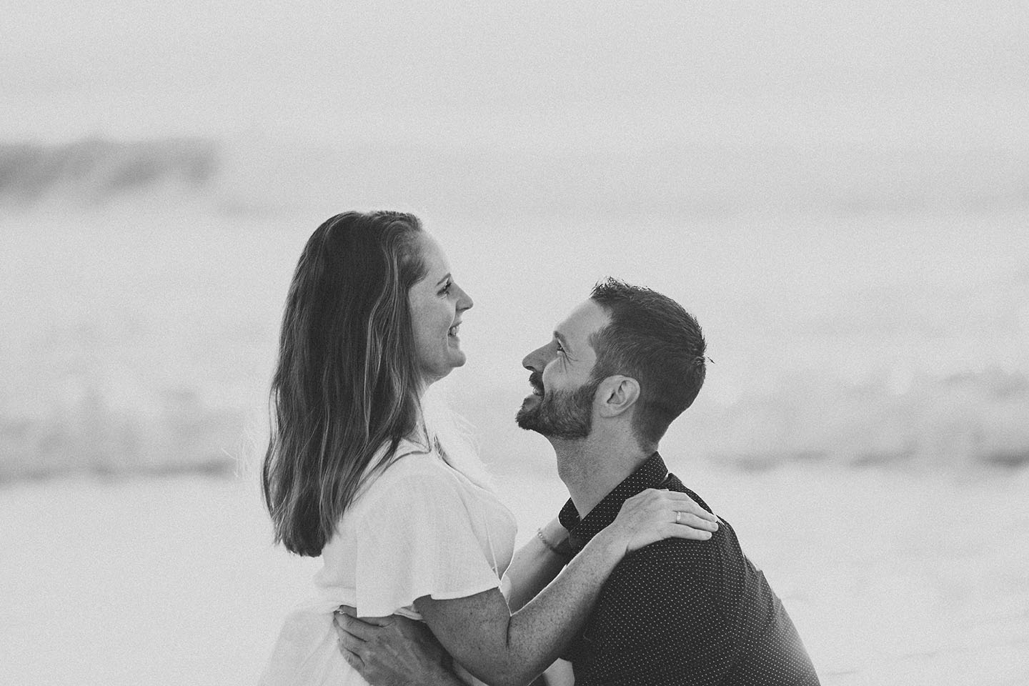 Engagement Photography - couple embracing on beach at sunset black and white