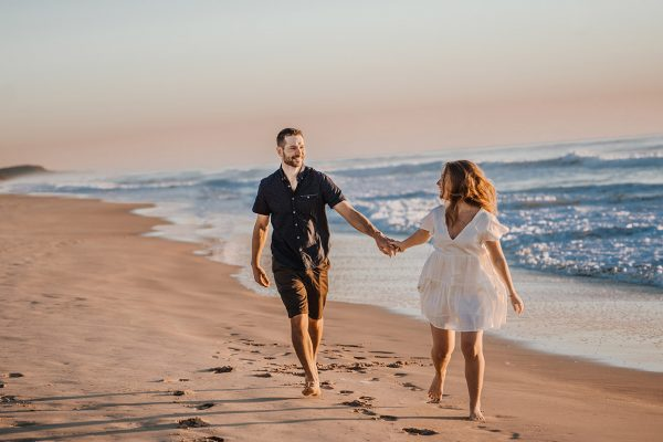 Engagement Photography couple holding hands on beach at sunset