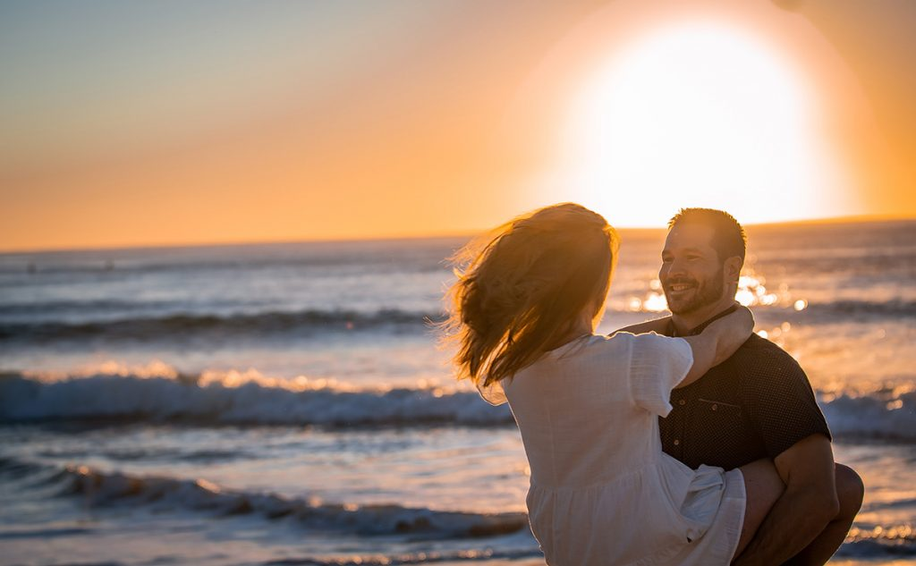 Engagement Photography - couple embracing on beach at sunset