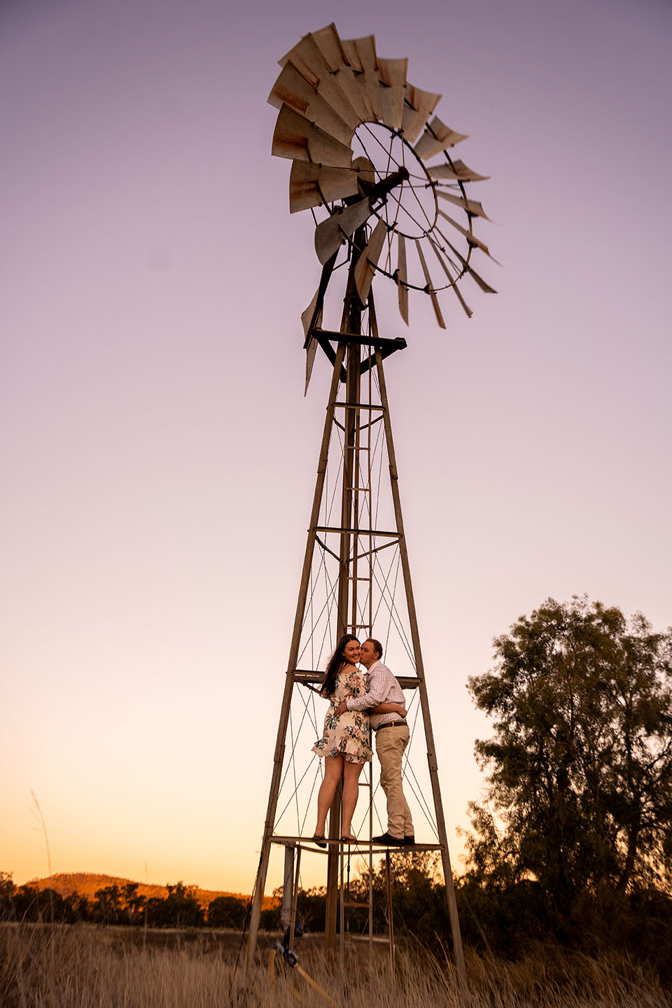 Engagement Photography - couple under windmill at sunset