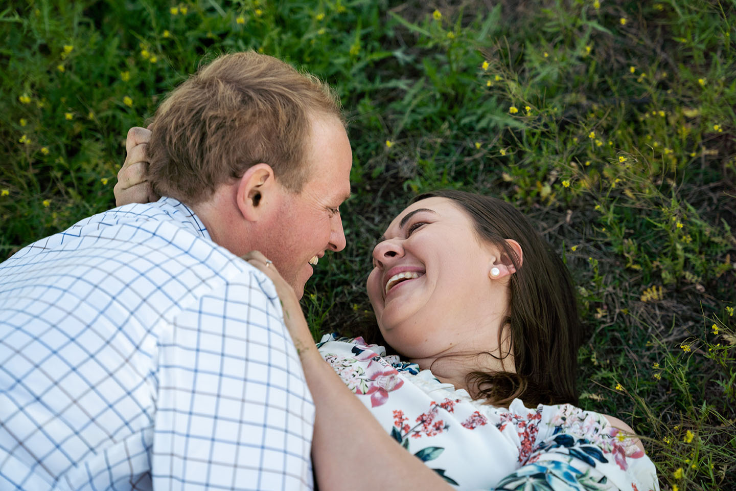 Engagement Photography - couple laying in grassy field