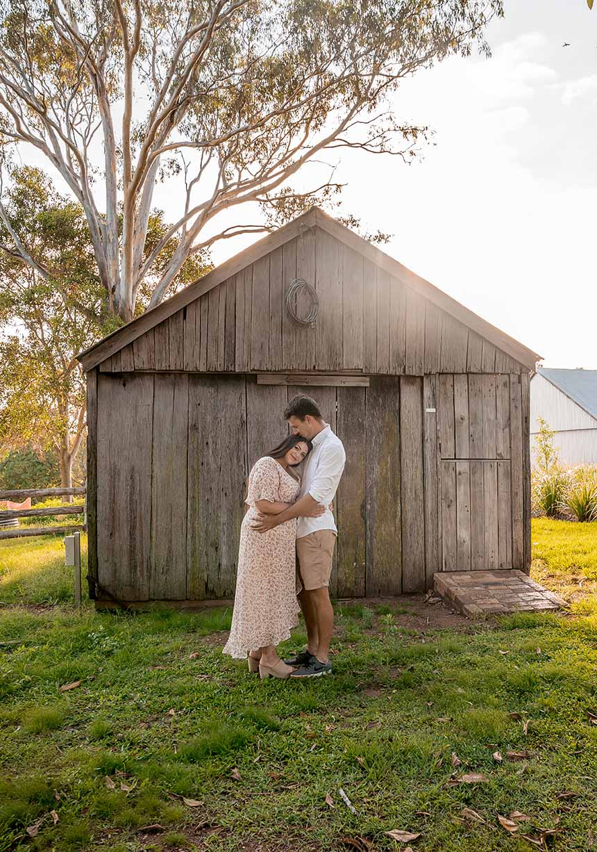 Family Photo - Husband and wife in front of rustic shed
