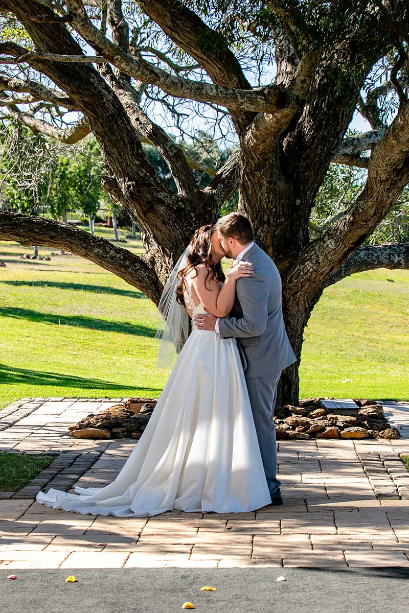 Wedding Photography - Husband and wife kissing under tree