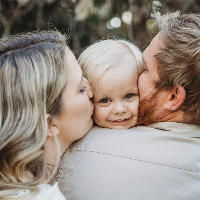 Family Photography - mother and father kissing sons cheek