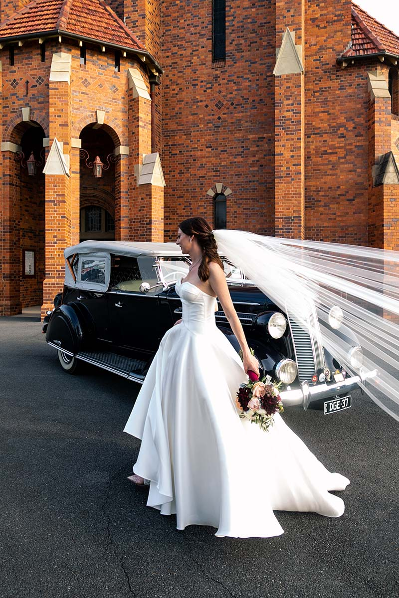 Wedding Photography - Bride in front of car and church