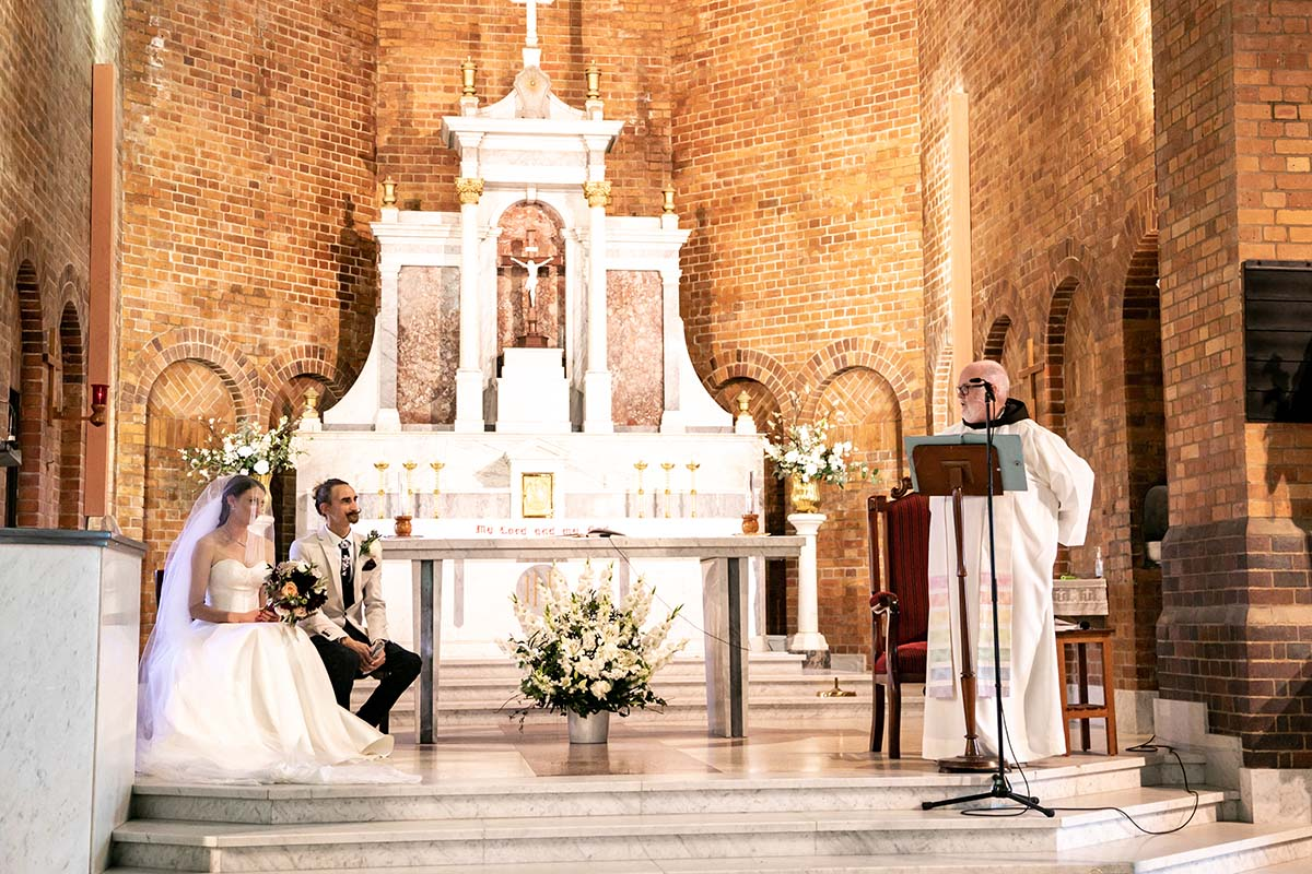 Wedding Photography - Ceremony couple sitting with Priest