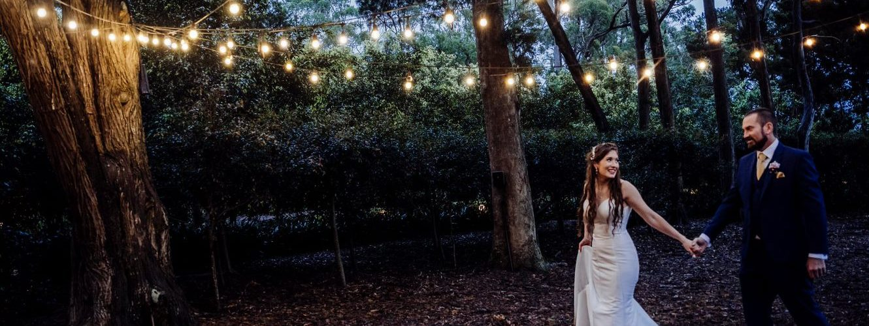 Wedding Photography Bride and Groom walking under twinkle lights