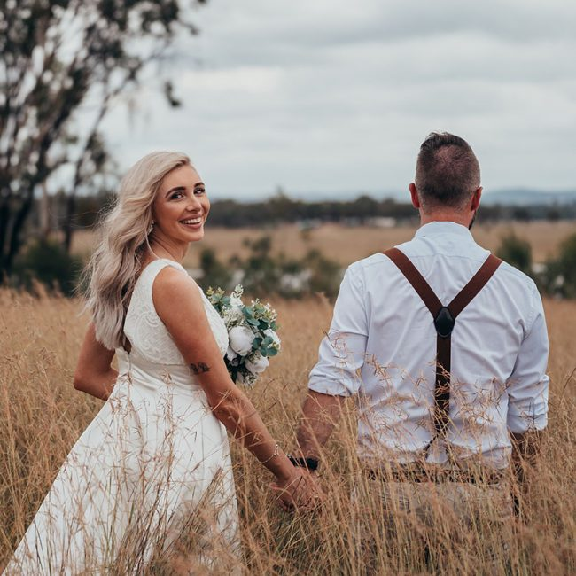Wedding Photography - couple walking in field
