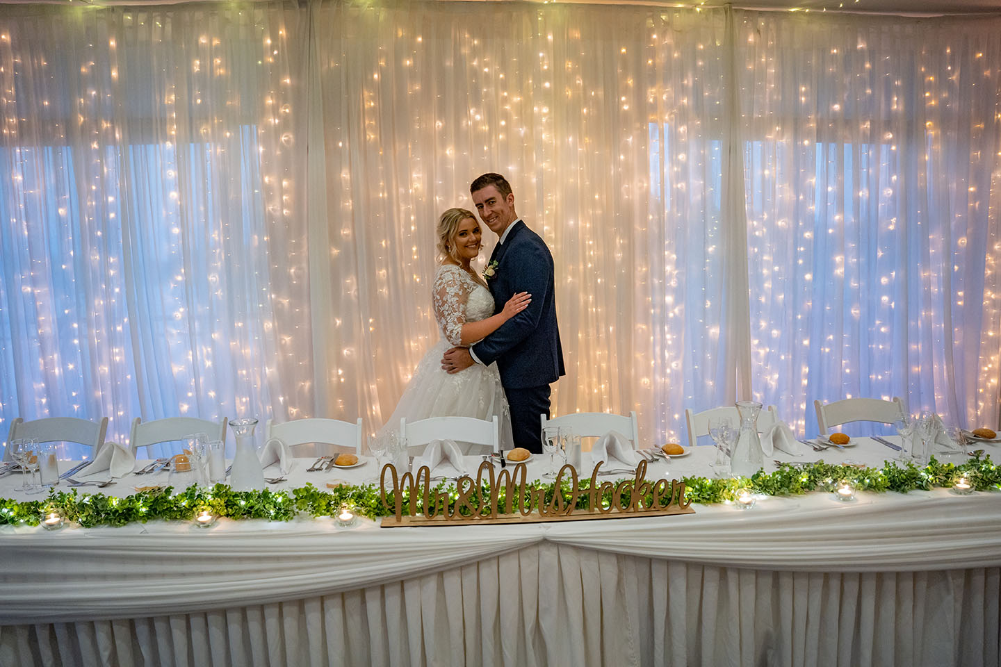 Wedding Photography - couple in front of wall of fairy lights