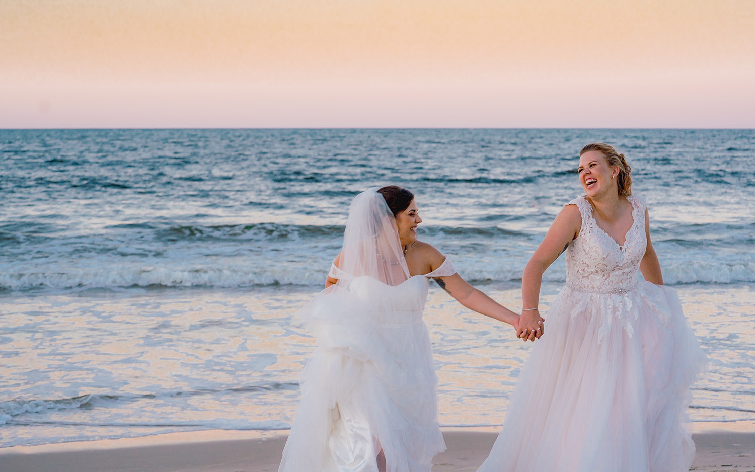 Wedding Photography - Brides holding hands on beach