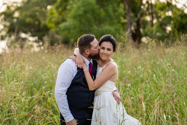 Wedding Photography - Cheek kisses in field