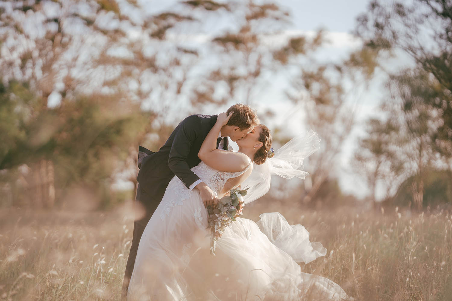 Wedding Photography - Kissing in field
