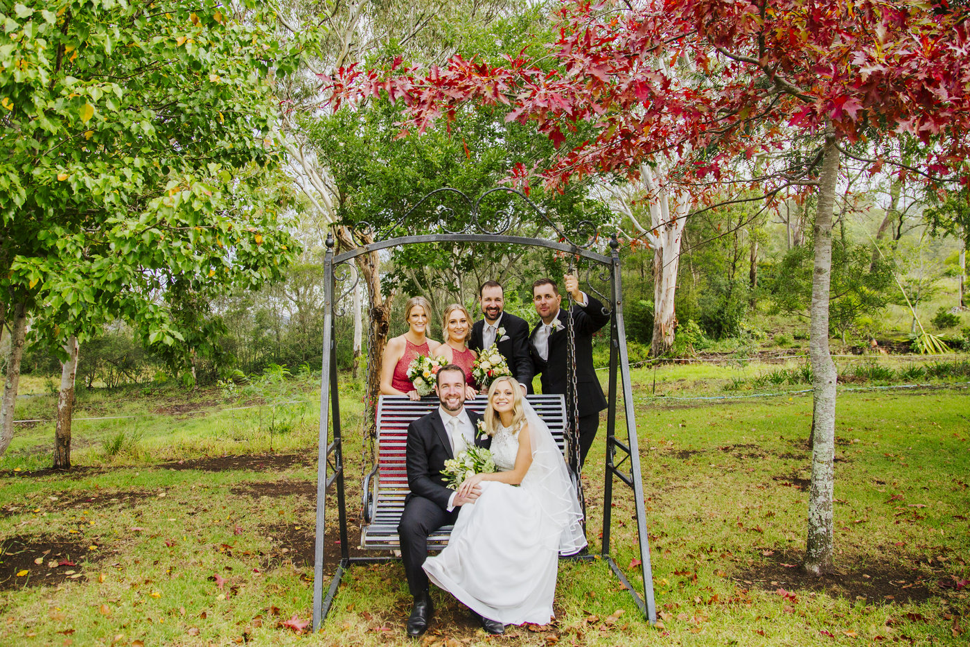 Wedding Photography couple on swing with bridal party